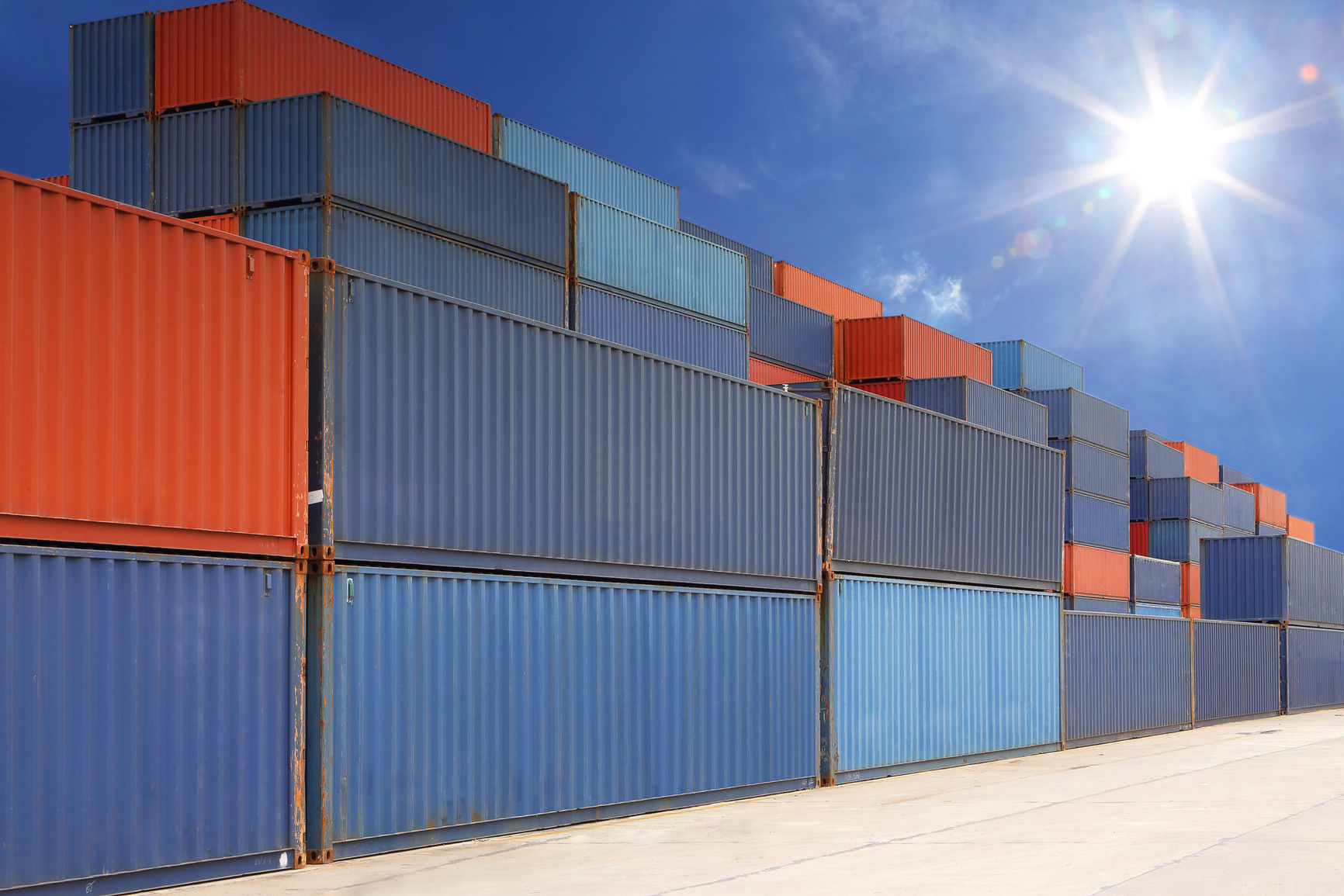photodune-5486478-stack-of-cargo-containers-at-container-yard-with-sunbeam-m